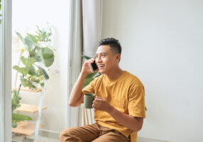 man on phone drinking tea